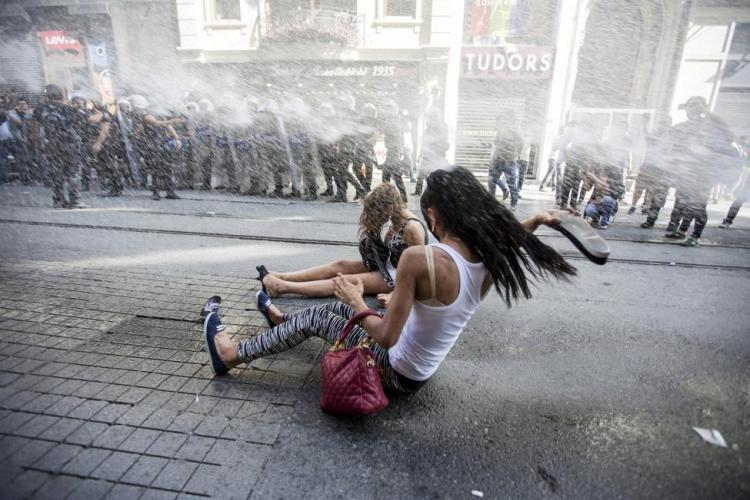 Riot police use a water cannon to disperse LGBT rights activists before a gay pride parade in central Istanbul, Turkey, June 28, 2015. Turkish police fired water cannon and rubber pellets to disperse a crowd gathered in central Istanbul for the city's annual gay pride parade, a Reuters cameraman at the scene said. The police appeared intent on stopping the crowd gathering near Taksim Square, the cameraman said. Taksim is a traditional rallying ground for demonstrators and saw weeks of unrest in 2013. REUTERS/Kemal Aslan